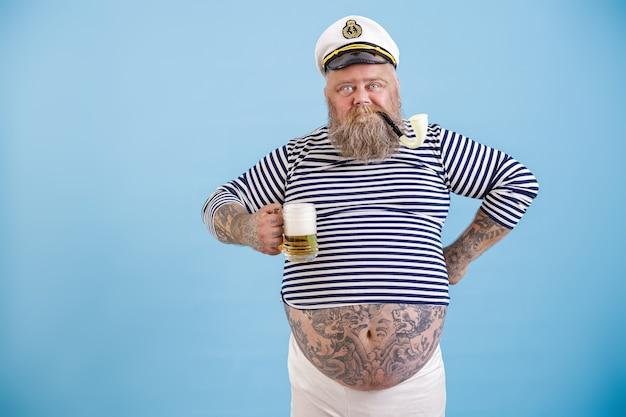 あごひげと喫煙パイプで太った船乗りをダッシュは、水色の背景に泡立ったビールを保持します