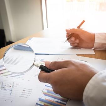 돋보기、ペン、電卓を使った外国為替市場でのデータ分析:紙のチャートと要約情報。技術分析のための金融商品の図表。