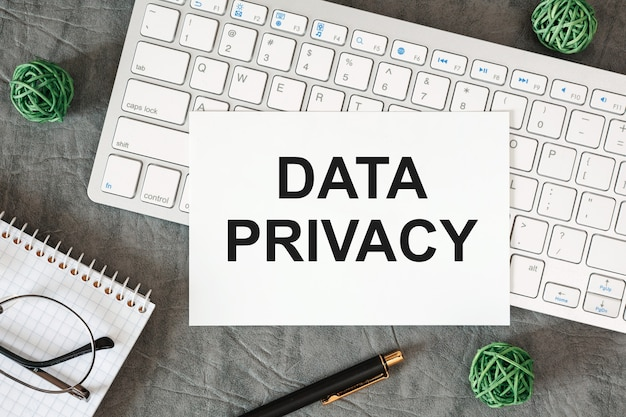 Data privacy is written in a document on the office desk with office accessories.