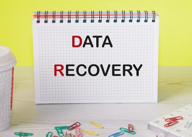 주위에 클립과 노란색 배경이있는 노트북의 데이터 복구 텍스트