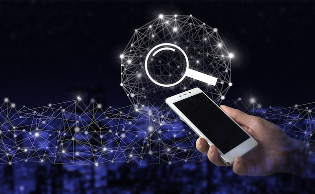 Data search technology search engine optimization. hand hold white smartphone with digital hologram search data sign on city dark blurred background. search data icon of internet browser.