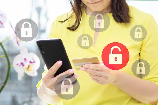 クレジットカードでオンラインで支払うときのデータセキュリティ。データ保護と安全なオンライン支払い。携帯電話とラップトップを使用して女性の手のクローズアップビュー。ロックのアイコンが付いた仮想画面