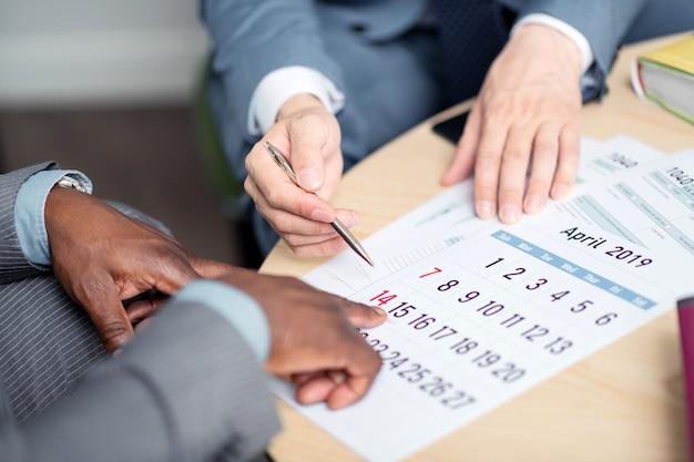 交渉の日付。交渉の次の日付を提案するペンを保持しているビジネスマンの上面図