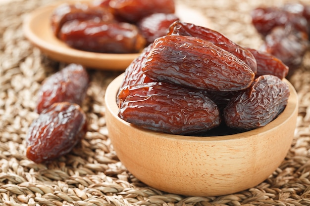 Date fruit in wood bowl on wicker placemat