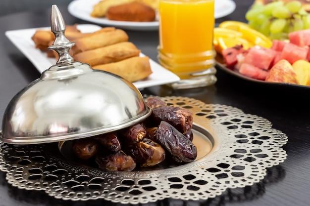 Date medjool palm fruits, fresh orange juice, samosa snack and fruit