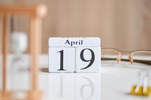 白い木製の立方体-4月19日、白いテーブルの上の日付。