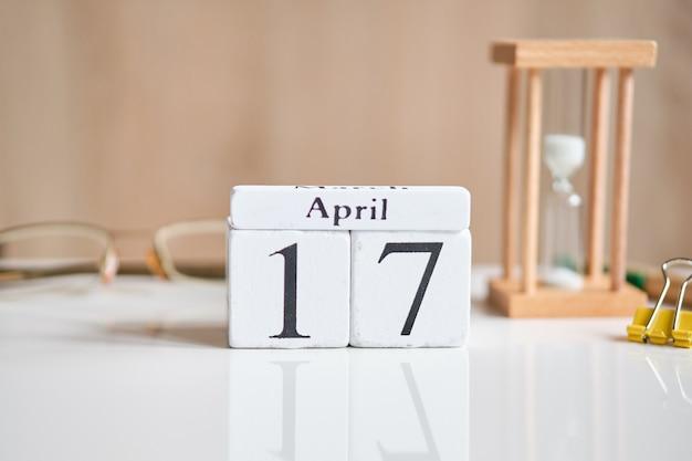 白い木製の立方体の日付-17、白いテーブルの4月17日。