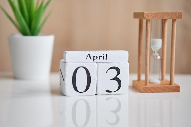 白い木製キューブの日付-3番目、4月3日、白いテーブル。