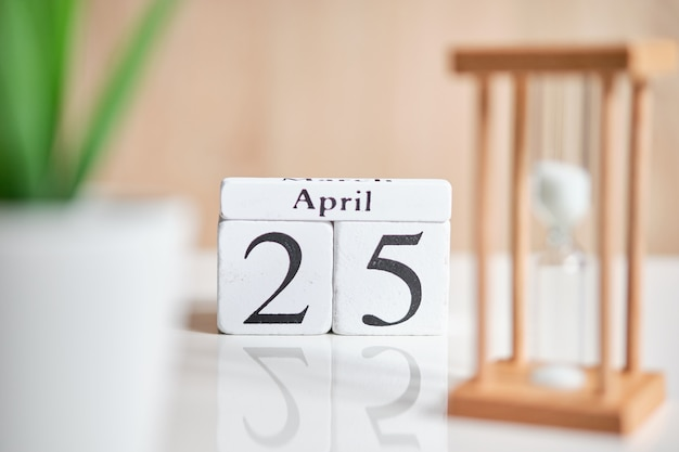 白い木製の立方体の日付-4月25日、25日、白いテーブル。