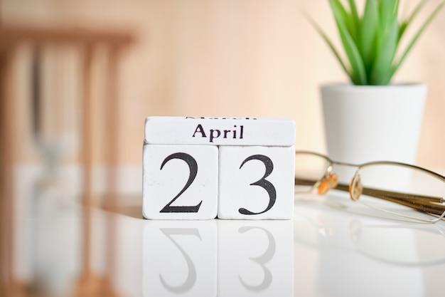 白い木製の立方体の日付-23日、4月23日、白いテーブル。