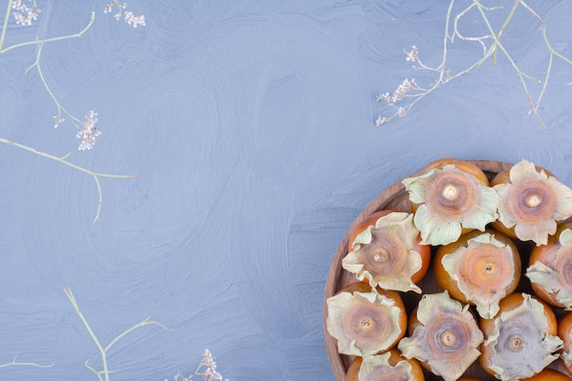 青い背景の上の木製の大皿にマメガキ