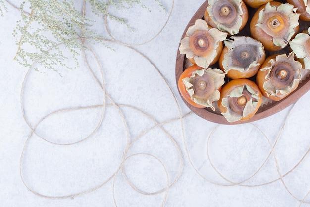 Финиковые сливы в деревянном блюде на сером фоне