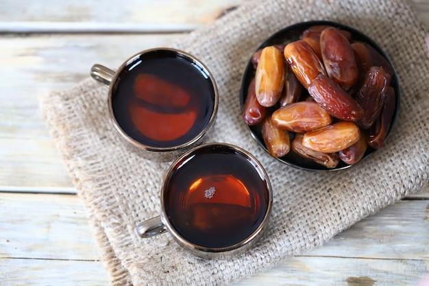 Финиковый чай финики в миске на деревянной поверхности