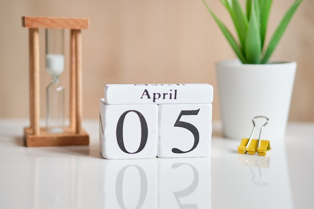 Date on white wooden cubes - the fifth, 05 april on a white table.