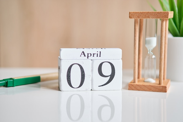 Date on white wooden cubes - the ninth, 09 april on a white table.