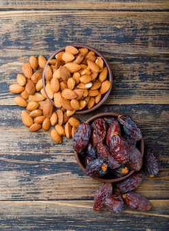 Dates and almonds in clay plates on wooden background, top view.