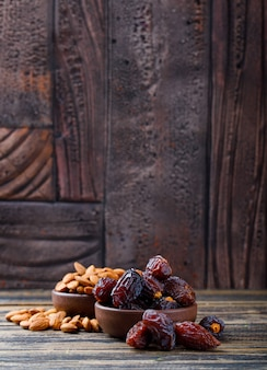 Dates and almonds in clay plates on wooden and stone tile background. side view.