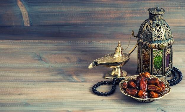 Dates, arabian lantern and rosary. islamic holidays concept. ramadan decoration. retro style toned picture