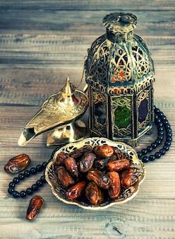 Финики, арабский фонарь и четки. восточный декор. тонированная картина в стиле ретро