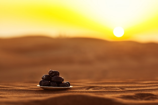 Dates on a beautiful plate in the desert at a beautiful sunset, symbolizing ramadan
