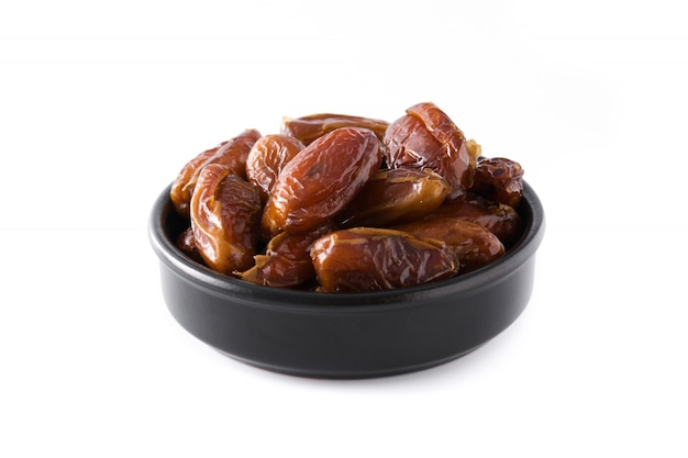 Dates in black bowl isolated on white