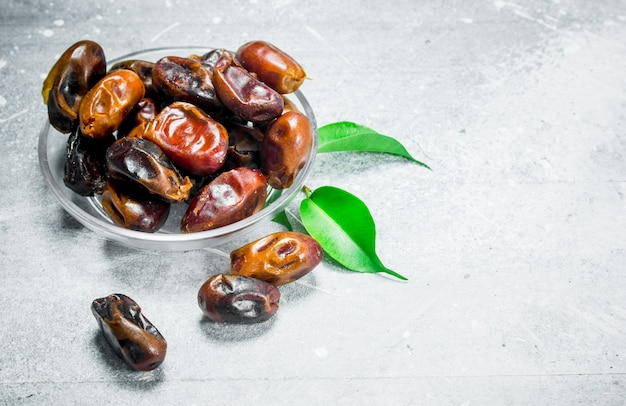 Dates in bowl. on a rustic table.