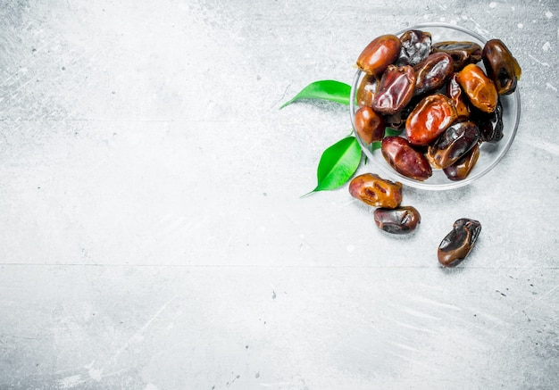 Dates in bowl on rustic table.