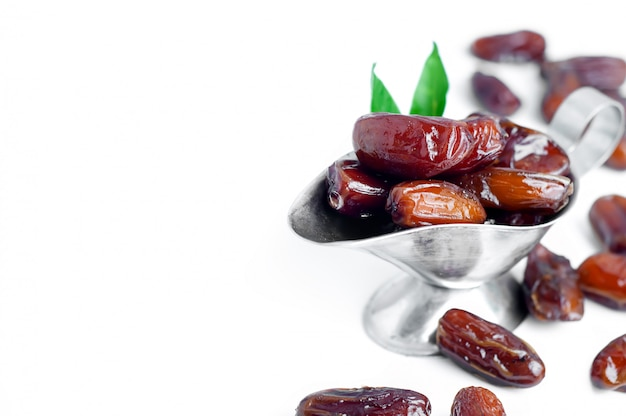 Dates in a bowl on white background.