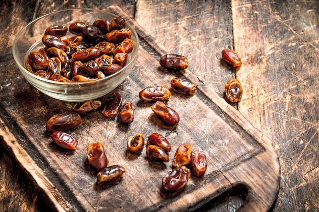 Dates in a bowl on wooden background