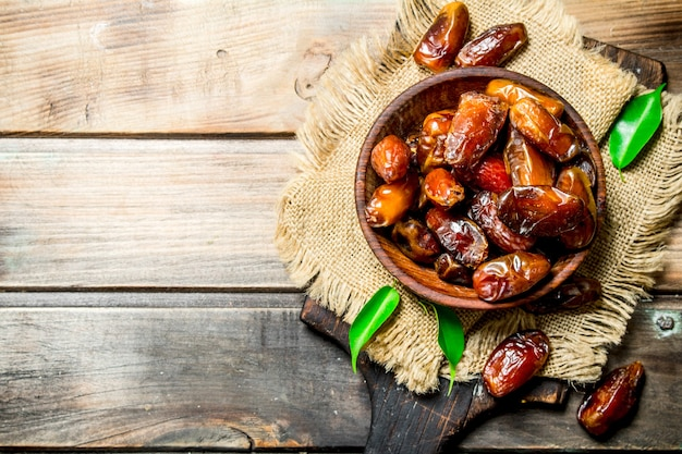 Dates in bowl on a wooden table.