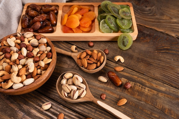 Dates, dried apricots and kiwis in a compartmental dish and assortment of nuts in wooden bowl on a dark wooden table.