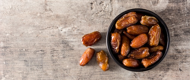 Dates food in black bowl on wooden table panorama view copy space