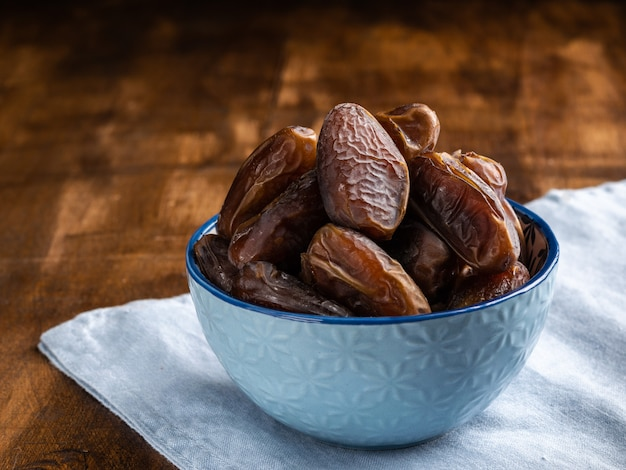 Dates of fruit in a blue ceramic bowl close up on wooden background.