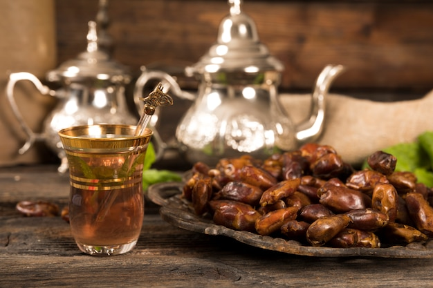 Dates fruit on plate with tea glass
