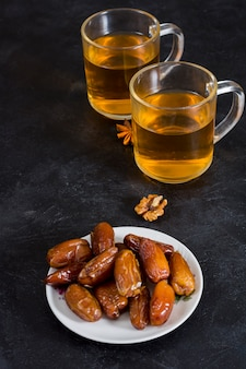 Dates fruit on plate with tea on table