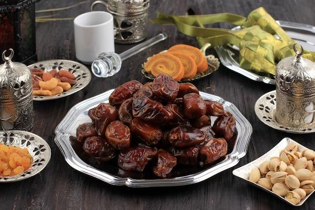 날짜 과일: 나무 테이블에 복사 공간이 있는 라마단 음식 및 음료 개념. 날짜 과일, 견과류, 씨앗, 커피, 차, honeyand ketupat. ied al fitr를 위한 아라비아 이슬람식 음식