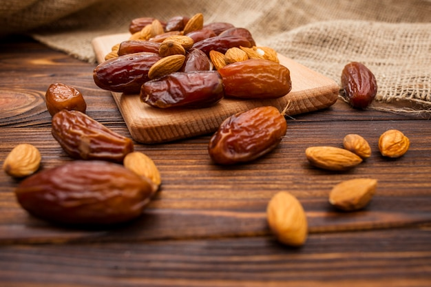 Dates fruit with almonds on wooden board