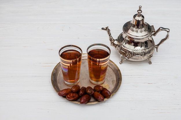 Dates fruit with glasses of tea on table