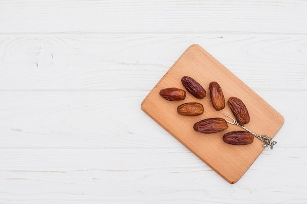 Dates fruit on wooden board on table