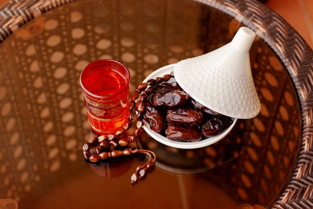 Dates in a glass plate with a lid, an oriental drink and a rosary on a glass table