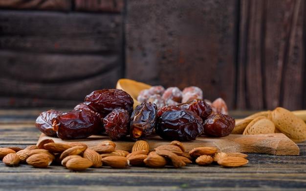 Финики в разделочной доске с очищенным и неочищенным миндалем, орехами в деревянной ложке, вид сбоку на фоне деревянной и каменной плитки
