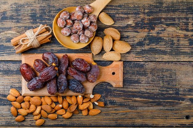 Финики на разделочной доске с очищенным и неочищенным миндалем, орехами в деревянной ложке, палочками корицы, вид сверху на деревянном фоне