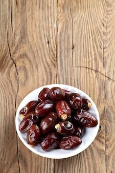 Финики на деревянном столе. фрукты сушеные финики.