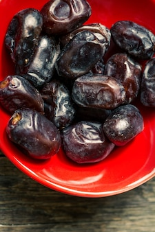 Dates in plate on wooden background