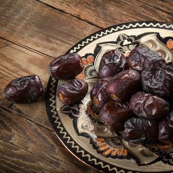 Dates in plate on wooden table