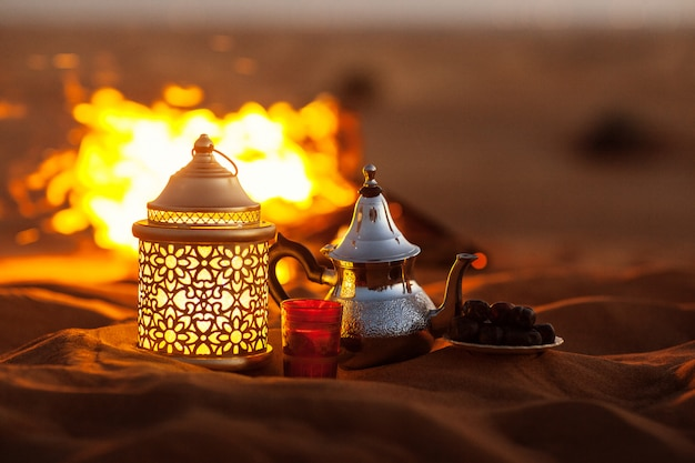 Dates, teapot, cup with tea near the fire in the desert with a beautiful background. ramadan kareem