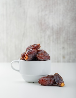 Dates in a white cup on grunge and white table. side view.