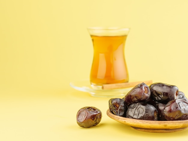 黄色の背景に紅茶とデート。ラマダン期間中の伝統的なイフタール料理。