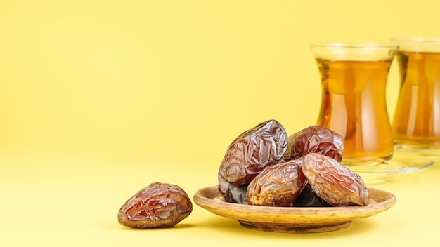 Dates with black tea on a yellow background. traditional iftar food during ramadan.