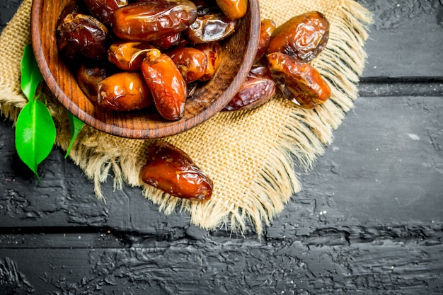 Dates with a bowl with green leaves. on black rustic table.